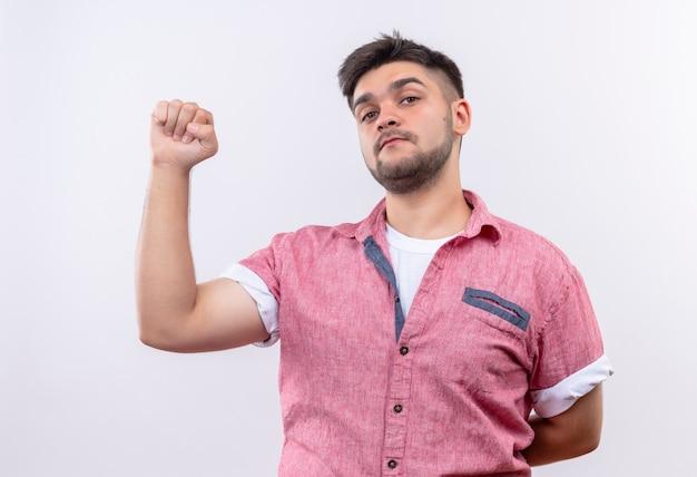 Jovem rapaz bonito vestindo uma camisa pólo rosa indo bem com o punho sério, olhando em pé sobre uma parede branca