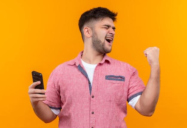 Jovem rapaz bonito vestindo uma camisa pólo rosa segurando o telefone feliz fazendo sinal com o punho em pé sobre a parede laranja