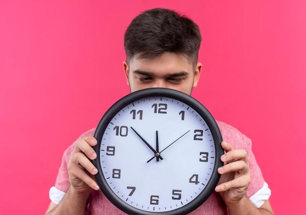 Jovem rapaz bonito vestindo uma camisa pólo rosa sonolento segurando um relógio pendurado na parede rosa