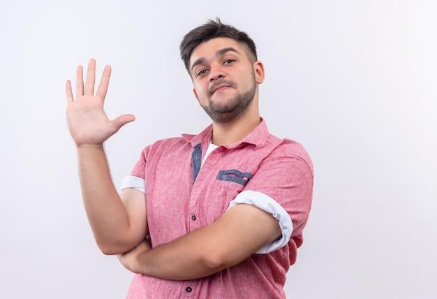 Jovem rapaz bonito vestindo uma camisa pólo rosa sorrindo e mostrando cinco com os dedos em pé sobre uma parede branca