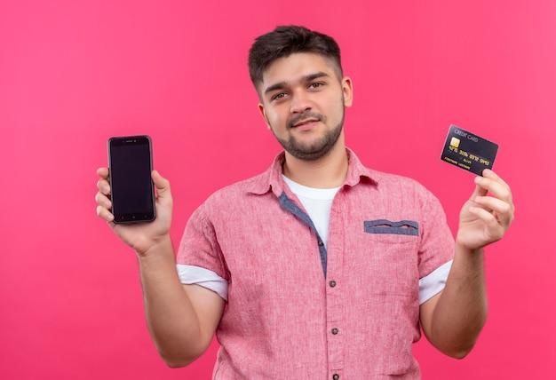 Jovem rapaz bonito vestindo uma camisa pólo rosa sorrindo, segurando o telefone e o cartão de crédito em pé sobre a parede rosa