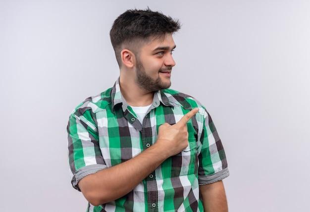 Jovem rapaz bonito vestindo uma camisa xadrez olhando além de apontar para a esquerda com o dedo indicador em pé sobre a parede branca