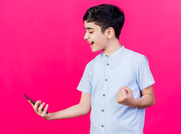Jovem rapaz caucasiano alegre segurando olhando para o celular, fazendo gesto de sim isolado no fundo carmesim
