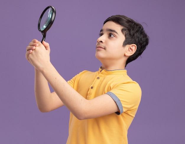 Jovem rapaz caucasiano impressionado segurando e olhando para o lado através de uma lupa isolada na parede roxa