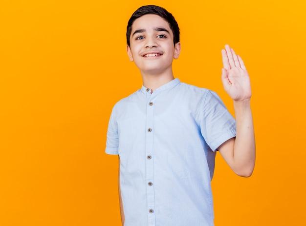 Jovem rapaz caucasiano sorridente, olhando para a câmera, fazendo gesto de olá, olhando para a câmera isolada em um fundo laranja com espaço de cópia