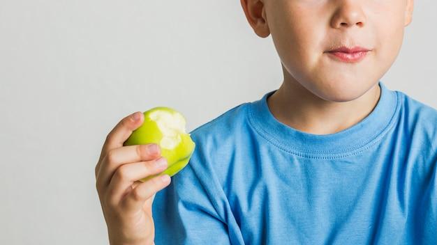 Jovem rapaz close-up com uma maçã verde