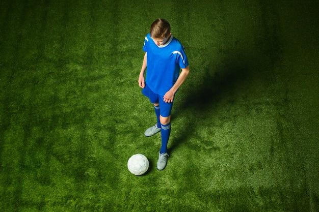 Jovem rapaz com bola de futebol, fazendo o chute voador