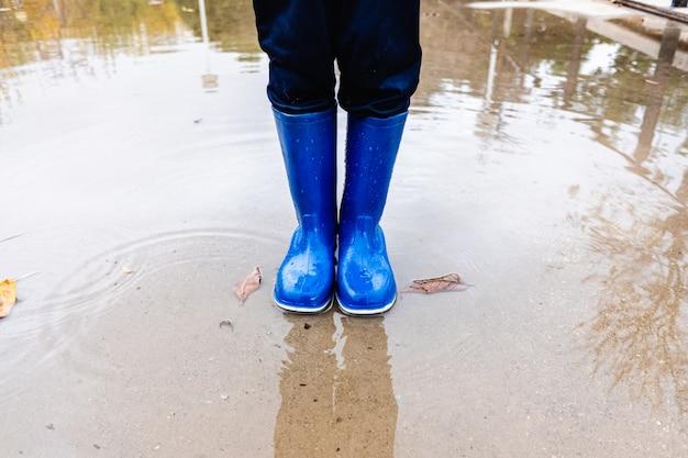 Jovem rapaz com botas de borracha azul salta sobre uma poça de água em um parque em sua cidade.