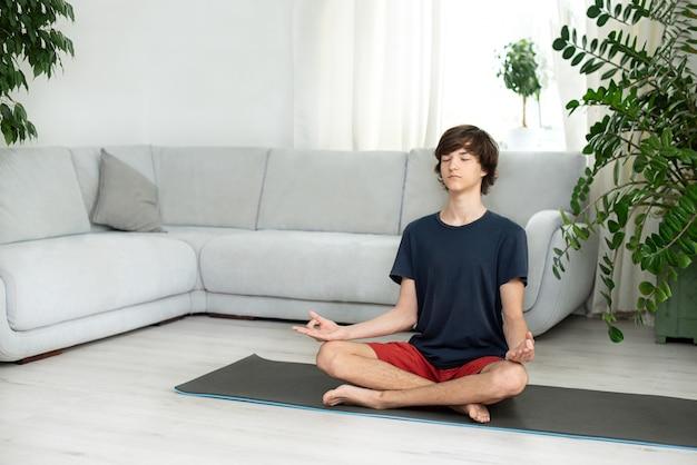 Jovem rapaz com cabelos longos faz yoga em casa