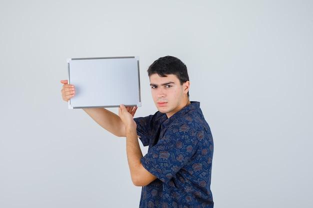 Jovem rapaz com camisa floral segurando whiteboard e olhando sério, vista frontal.