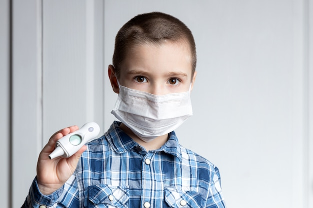 Jovem rapaz com olhos doloridos em uma máscara médica segurando um termômetro. proteção médica