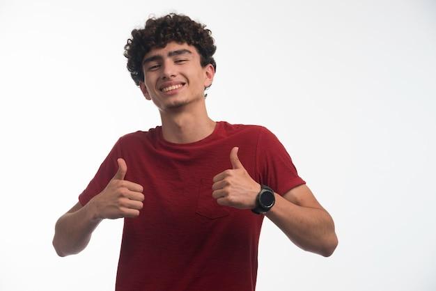 Jovem rapaz com penteado encaracolado, fazendo o polegar para cima.