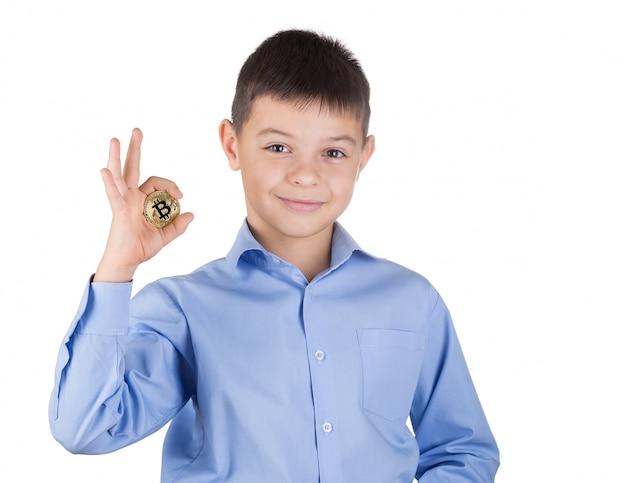 Jovem rapaz de camisa azul tem bitcoin na mão e sorri