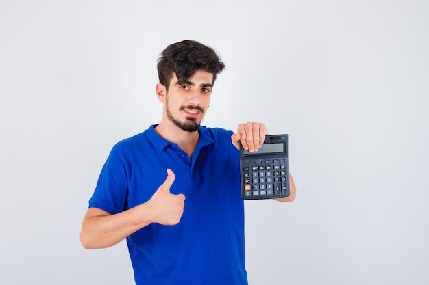 Jovem rapaz de camiseta azul segurando calculadora e mostrando o polegar para cima e parecendo feliz, vista frontal.