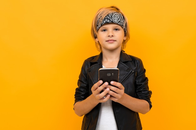 Jovem rapaz elegante em jaqueta preta e camiseta branca servindo a internet com o telefone