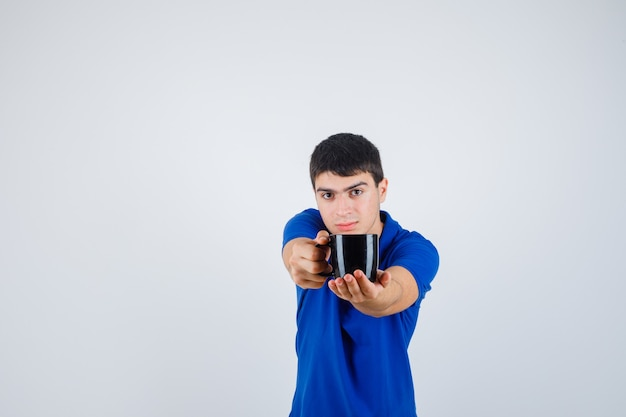 Jovem rapaz em t-shirt azul segurando copo, dando a alguém e olhando confiante, vista frontal.