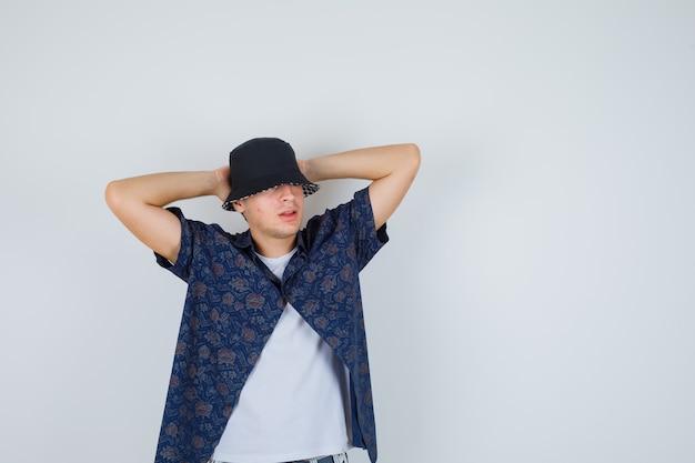 Jovem rapaz em t-shirt branca, camisa floral, boné de mãos dadas atrás da cabeça e olhando confiante, vista frontal.