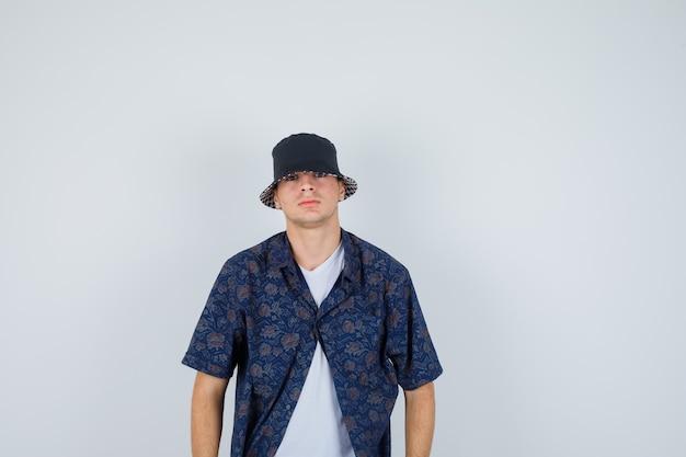 Jovem rapaz em t-shirt branca, camisa floral, boné reto e posando para a câmera e olhando confiante, vista frontal.