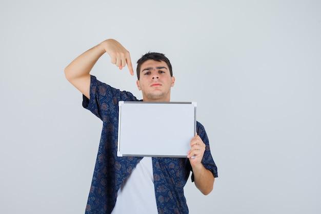 Jovem rapaz em t-shirt branca, camisa floral segurando whiteboard, apontando para ele com o dedo indicador e olhando sério, vista frontal.