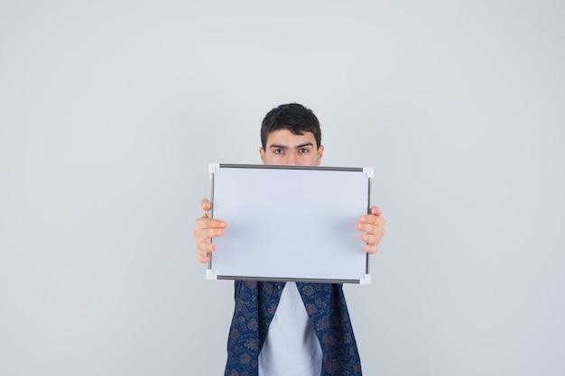 Jovem rapaz em t-shirt branca, camisa floral segurando whiteboard e olhando sério, vista frontal.