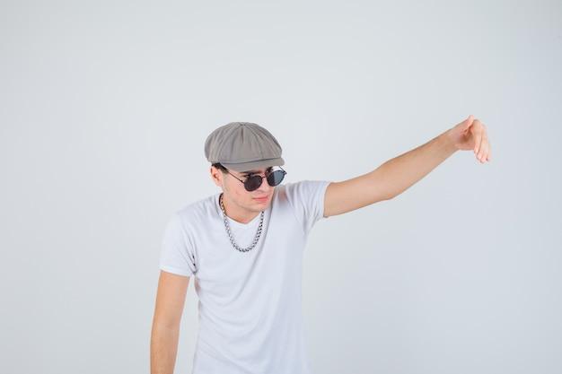 Jovem rapaz em t-shirt, chapéu convidando para vir e parecendo confiante, vista frontal.