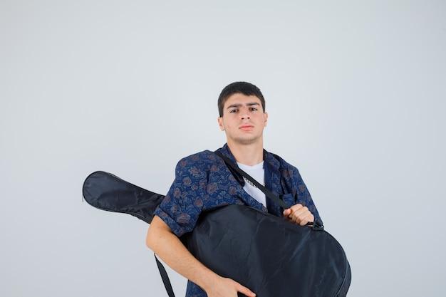 Jovem rapaz em t-shirt segurando guitarra, olhando para a câmera e olhando sério, vista frontal.