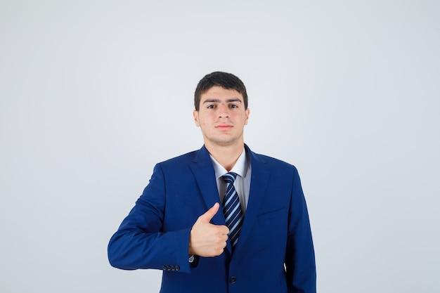 Jovem rapaz em terno azul formal aparecendo o polegar e olhando sério, vista frontal.