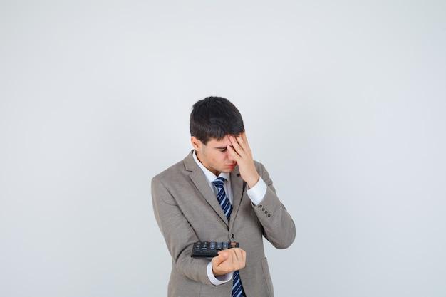 Jovem rapaz em um terno formal, segurando a calculadora, segurando a mão na testa e parecendo irritado, vista frontal.