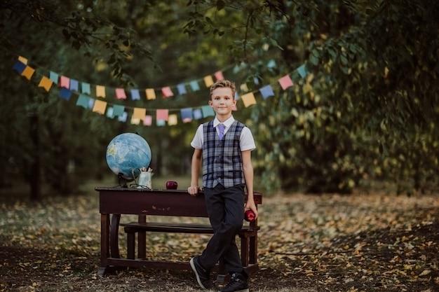 Jovem rapaz em uniforme escolar posando perto de uma velha mesa de madeira no parque