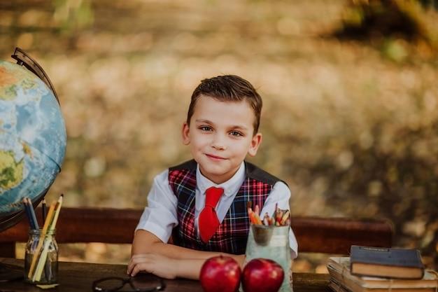 Jovem rapaz em uniforme escolar posando sentado em uma mesa de madeira velha no parque