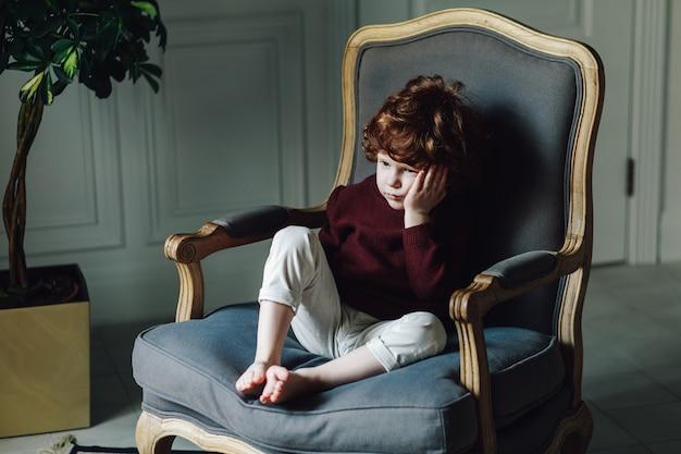 Jovem rapaz encostado na mão enquanto está sentado na poltrona. olhando thoughtul e um pouco triste