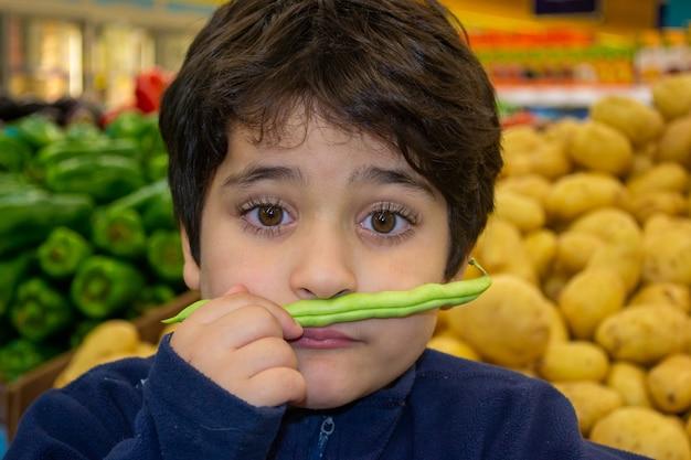 Jovem rapaz engraçado fazendo uma careta. ele segura uma vagem de ervilhas verdes como bigode.