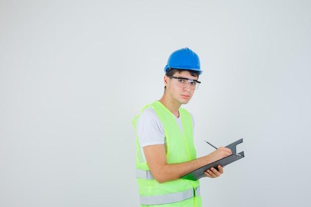 Jovem rapaz escrevendo notas na pasta de arquivo, olhando para a câmera em uniforme de construção e olhando com foco. vista frontal.