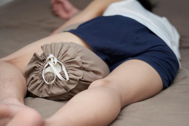 Jovem rapaz está dormindo em uma cama em casa e ele abraça o travesseiro.