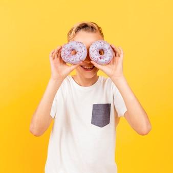 Jovem rapaz fazendo óculos com donuts