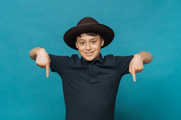 Jovem rapaz isolado na parede azul no chapéu marrom com uma aba e uma camiseta azul escura, apontando para baixo. olha ai por favor