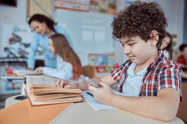 Jovem rapaz jogando lição de choramingar de smartphone. crianças do ensino fundamental sentadas em mesas e lendo livros em sala de aula.