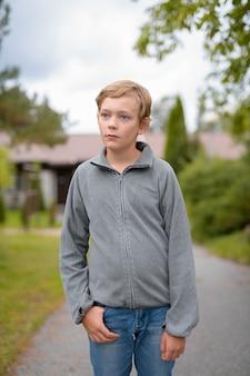 Jovem rapaz loiro bonito pensando em pé na casa do outdoo