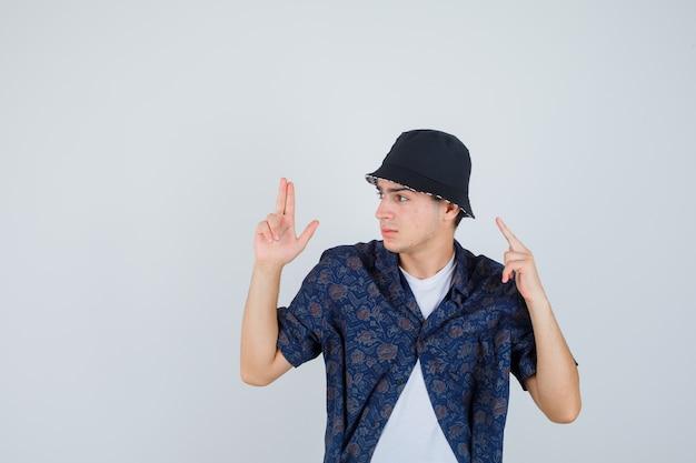 Jovem rapaz mostrando o gesto da arma, levantando o dedo indicador em uma camiseta branca, camisa floral, boné e parecendo confiante. vista frontal.