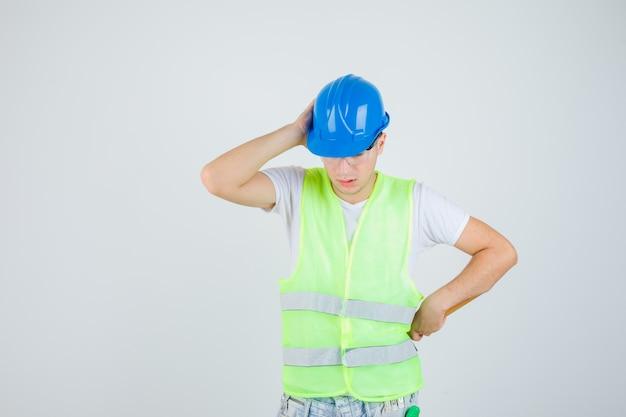 Jovem rapaz pressionando a mão na orelha, colocando a mão no quadril, segurando o martelo em uniforme de construção e olhando pensativo, vista frontal.