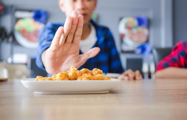 Jovem rapaz rejeitando a comida