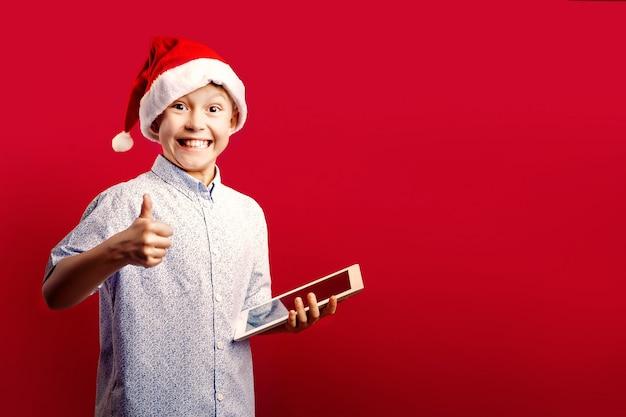 Jovem rapaz santa, fazendo okey polegares para cima gesto, mantendo um