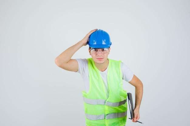 Jovem rapaz segurando a prancheta e a caneta, colocando a mão no capacete em uniforme de construção e parecendo confiante, vista frontal.