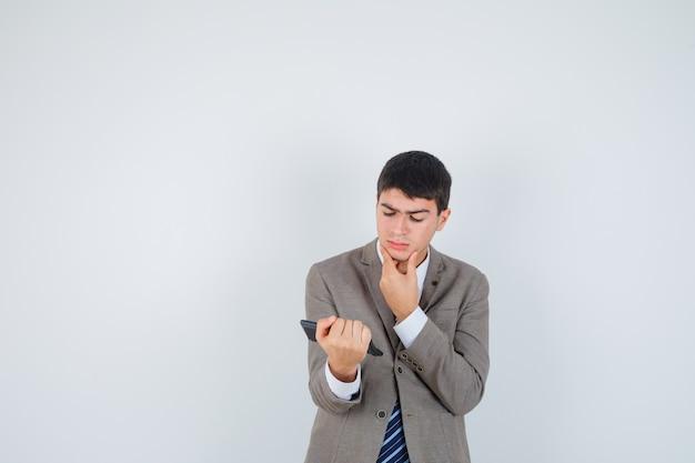 Jovem rapaz segurando calculadora, apoiando o queixo na mão em um terno formal e olhando pensativo, vista frontal.