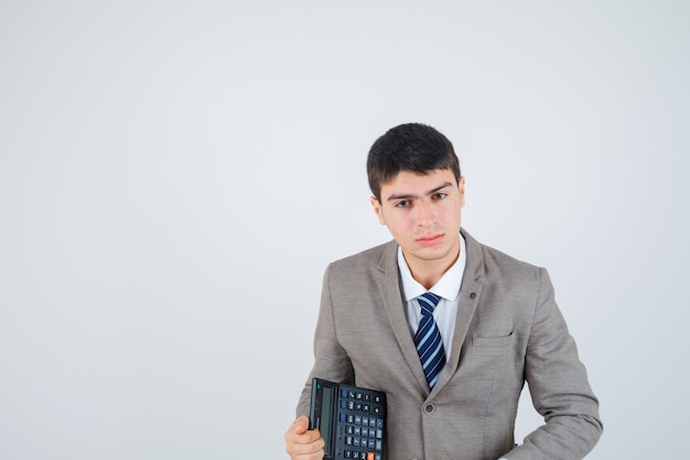 Jovem rapaz segurando calculadora em terno formal e olhando bonito, vista frontal.