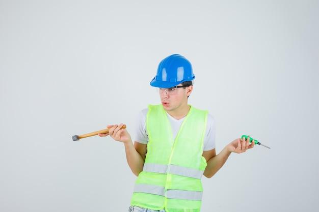 Jovem rapaz segurando o martelo e a chave de fenda em uniforme de construção e parecendo indeciso. vista frontal.
