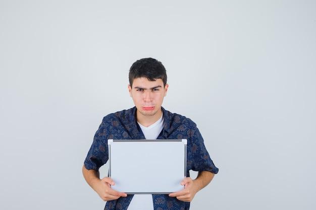 Jovem rapaz segurando o quadro branco, curvando os lábios em uma camiseta branca, camisa floral e parecendo triste, vista frontal.