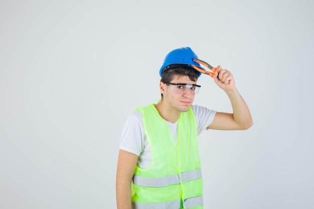Jovem rapaz segurando uma pinça perto da cabeça com uniforme de construção e olhando confiante, vista frontal.