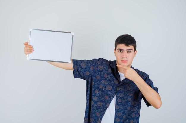 Jovem rapaz segurando whiteboard, apontando para ele em t-shirt branca, camisa floral e olhando sério, vista frontal.
