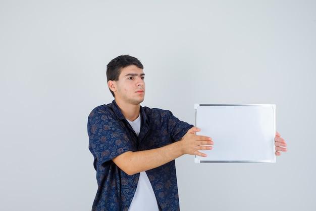 Jovem rapaz segurando whiteboard em t-shirt branca, camisa floral e olhando sério. vista frontal.